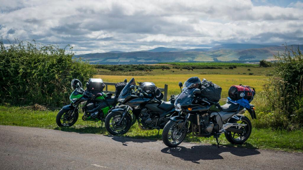 Die Motorräder vor einem schönen Feld und Berg Panorama.
